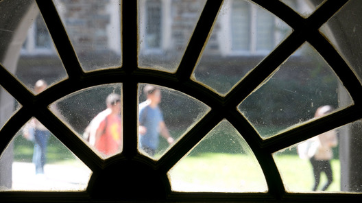students outside on a sunny day through a window