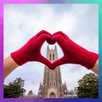 red gloved hands making a heart around the top of the duke chapel from afar