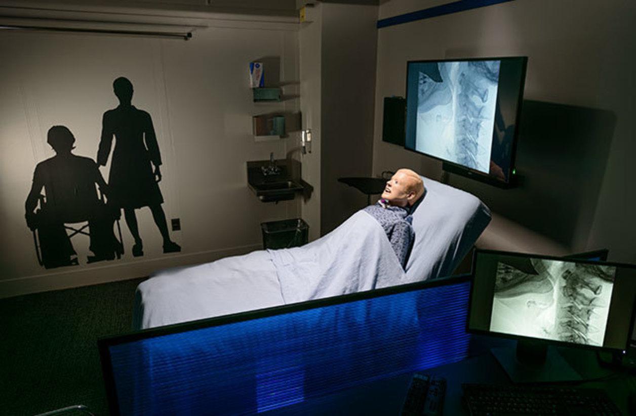 speech-language pathology simulation lab with manikin lying in hospital-style bed