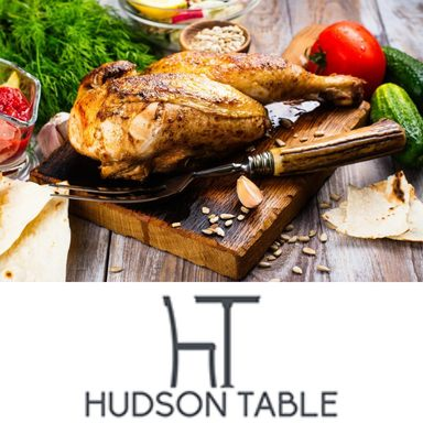 Hudson Table's gourmet roast chicken on a cutting board. Part of the Dinner and a Show package!