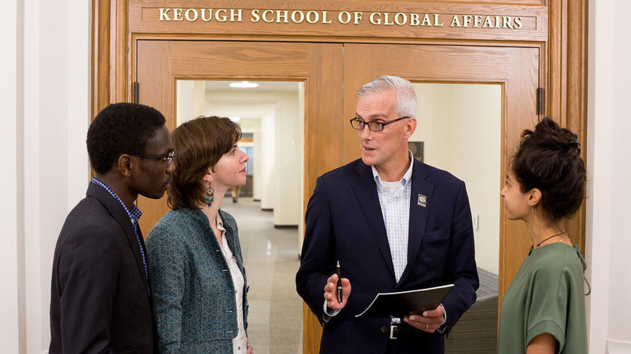 Photo of Denis McDonough speaking with three other people