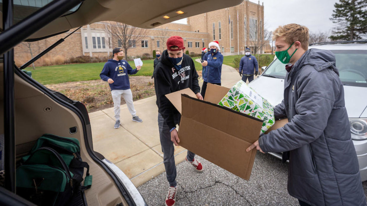 Photo of student athletes loading presents into a vehicle.