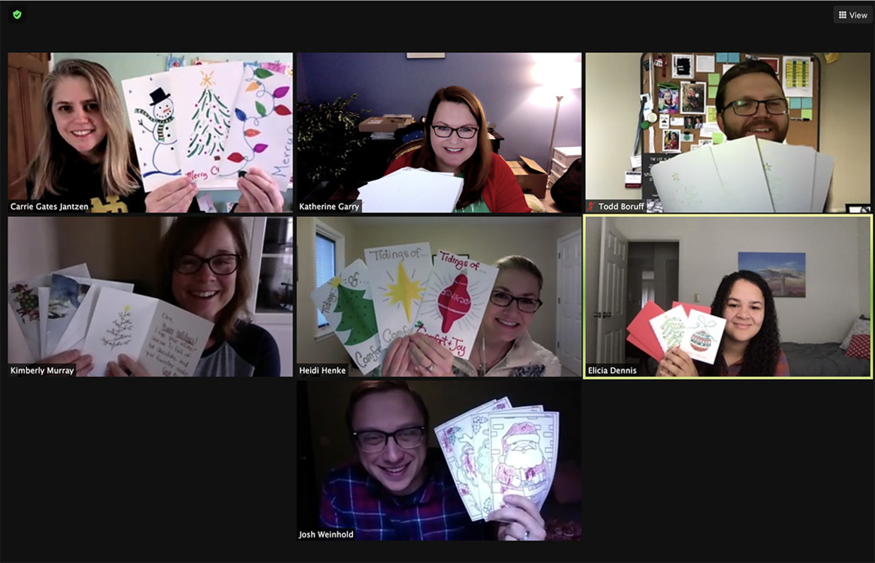 Photo of seven people on a zoom call holding up Christmas cards