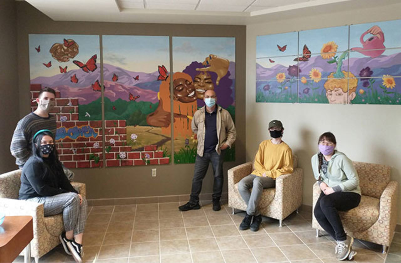 Students pose next to mural, which features outdoor scenes with butterflies and people