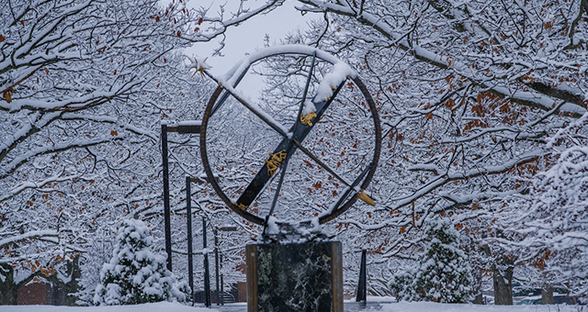 The Miami compass sculpture covered by snow and surrounded by winter trees
