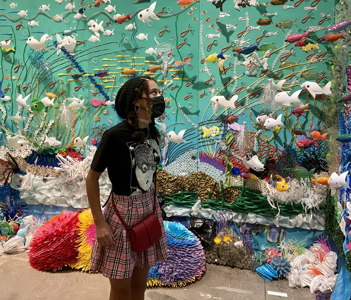 masked visitor at plastic coral reef installation