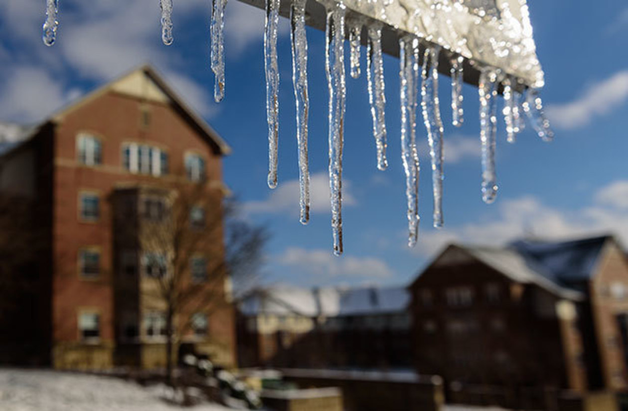 Icicles hanging from a sign with Putt and Ruddock halls in the background