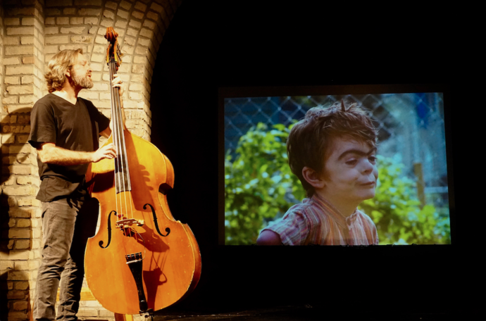 Matt Guidry, a tall slender man with long silver hair, stands on a stage with an upright bass, singing to an image of his son, Caleb, projected large on the wall behind him.