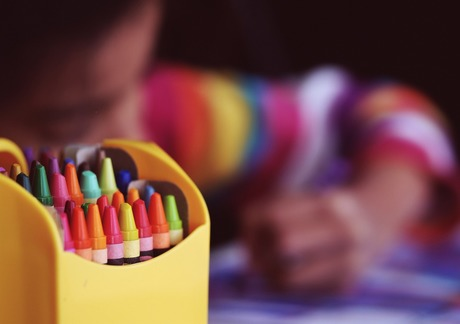 stock photo of child drawing in background with crayons in foreground