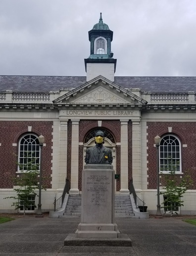 Photo of RA Long statue outside the library, with RA Long wearing a yellow mask