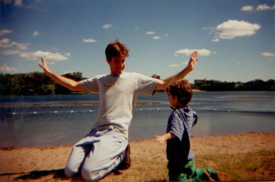 A photograph taken in 1998 of Matt Guidry on the beach with his son, Caleb, then 7 years old. Matt raises his arms in the air, and Caleb mimics.