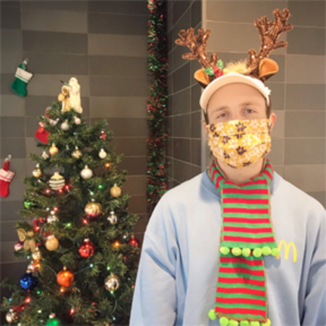 A young man wearing costume reindeer antlers and a fun holiday scarf.