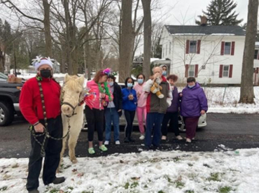 A group pictured with a pony.