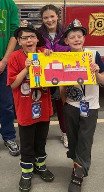 Children in an afternoon respite program visiting a firetwuck and displaying a picture they dre of a firetruck.