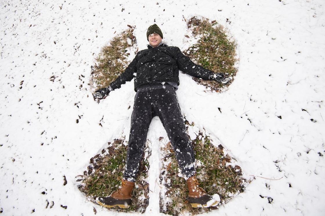 Man making snow angel on the ground