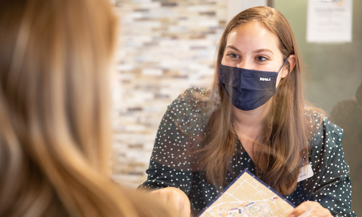 An NAU student worker, wearing an NAU mask, assisting a student checking into their campus residence hall.