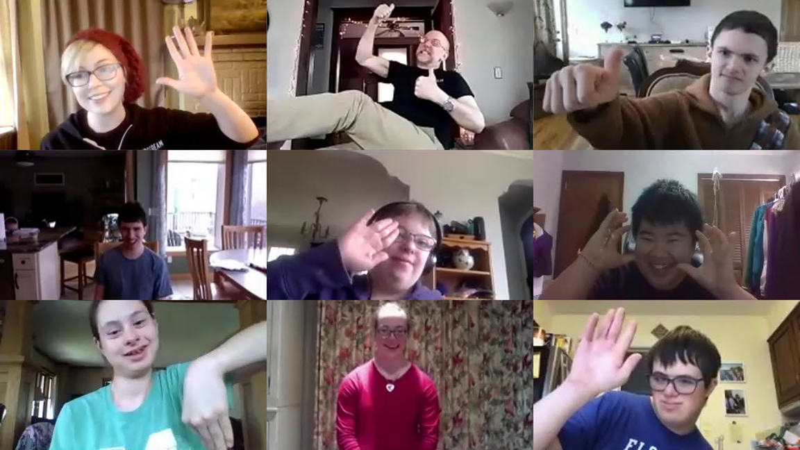 A Zoom screenshot of one of our online classes for and with adults with disabilities. The screenshot shows nine panels - each with a person smiling and creating a gesture, some with their hands raised like a wave, others holding up a thumbs up.