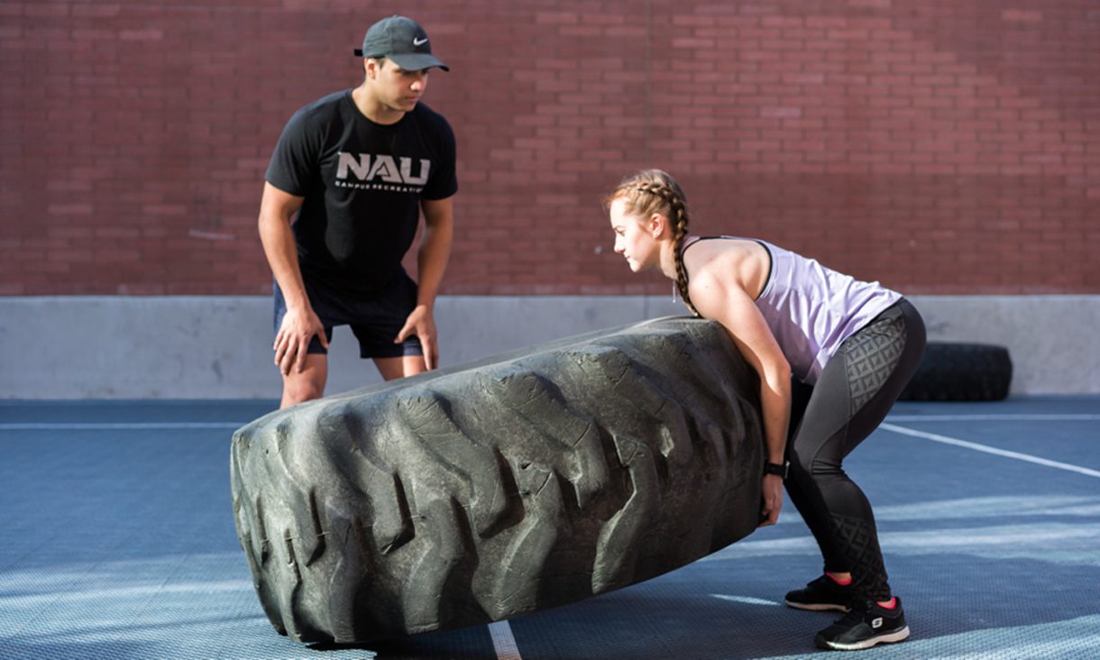 An NAU student personal trainer working with a client outdoors using a large tire for strength training.
