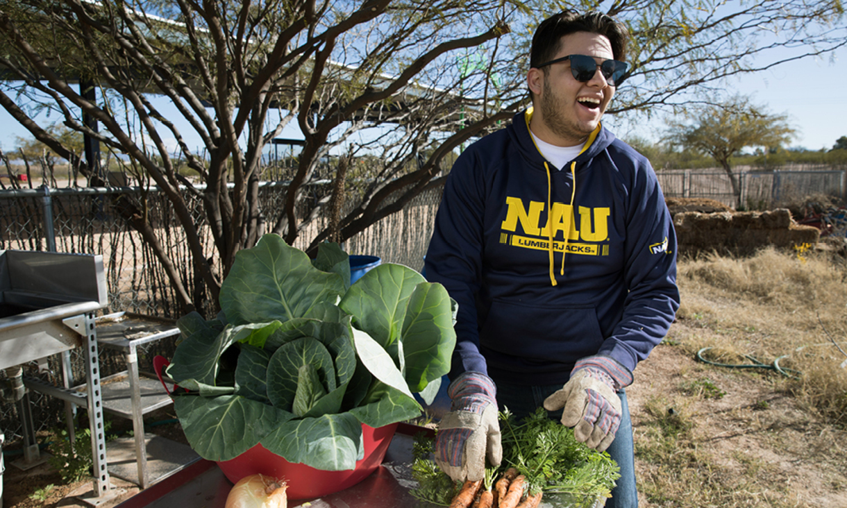 NAU student participating in an outdoor event in a community garden.
