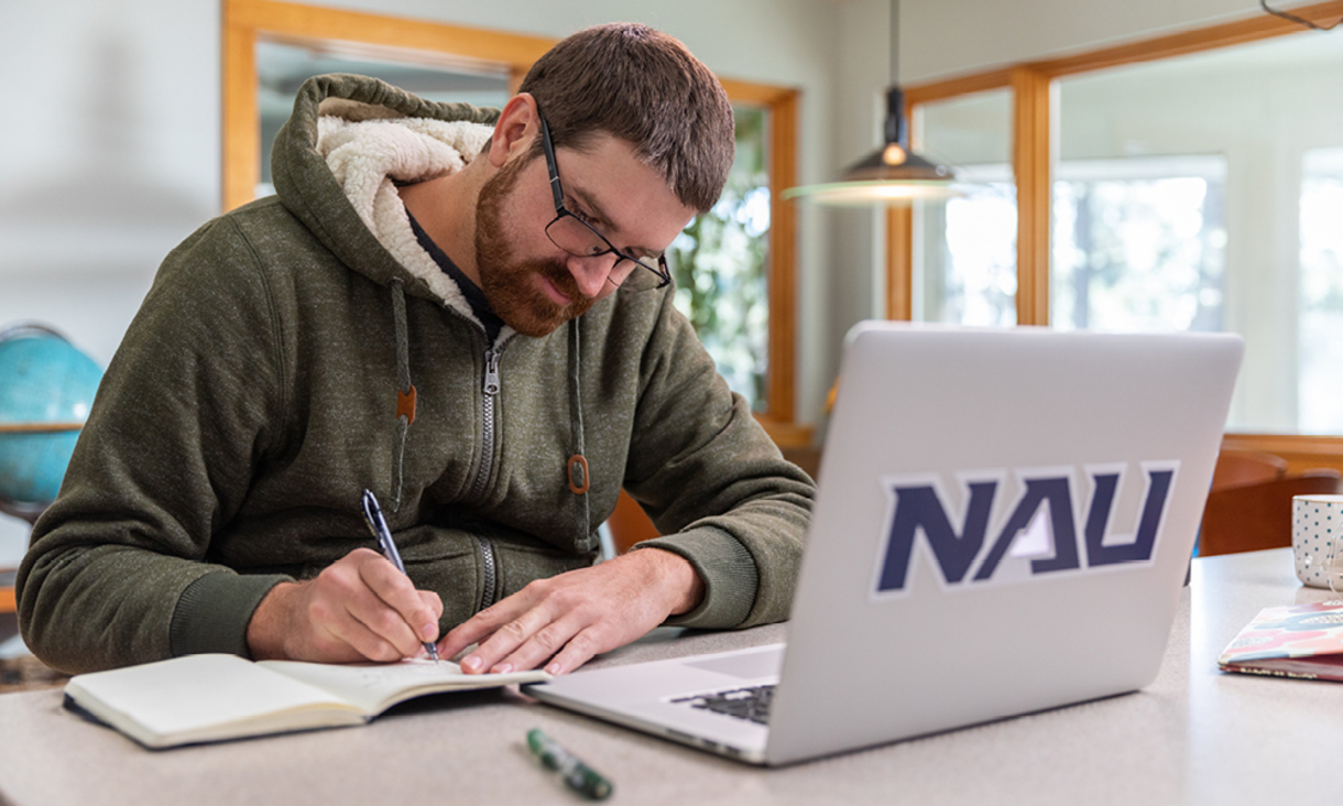 An NAU student applying for scholarships using a laptop at home.