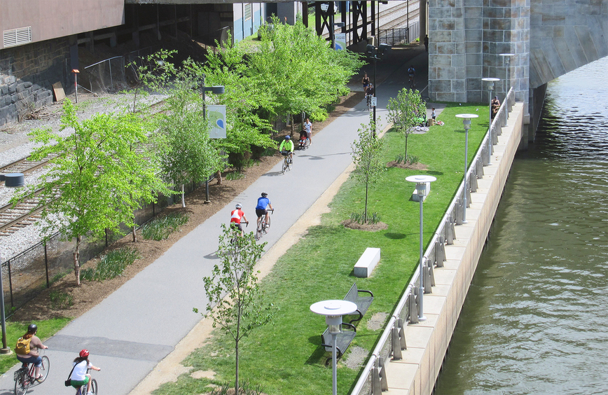 A paved path is used by bikers and walkers, it is lined with small trees, grass strips and benches. A contained river flows by under an overpass bridge.