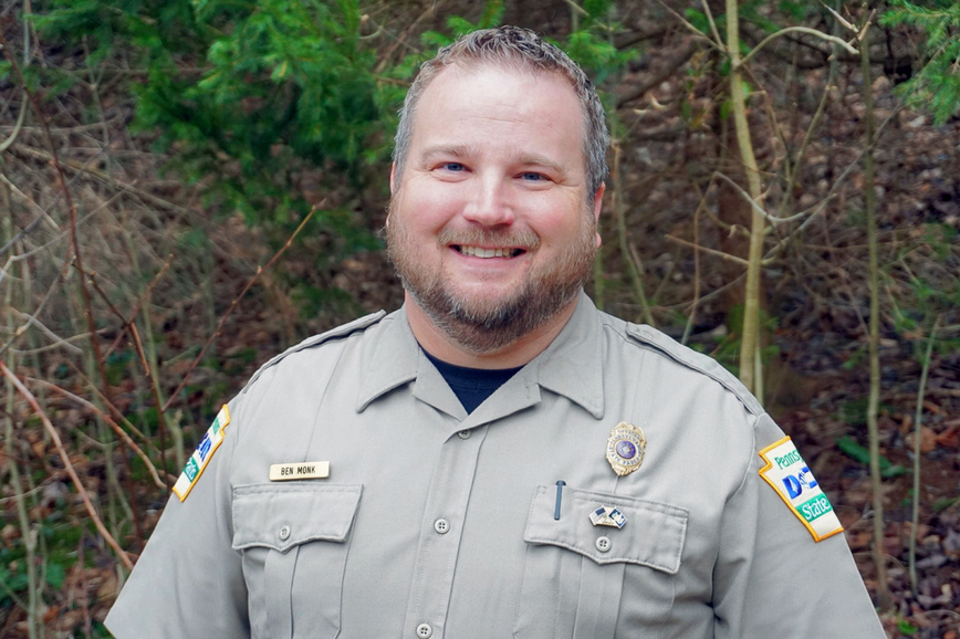 A man with dark hair and beard wears a tan DCNR uniform with a name bage and patches, stands in front of some trees and shrubs.