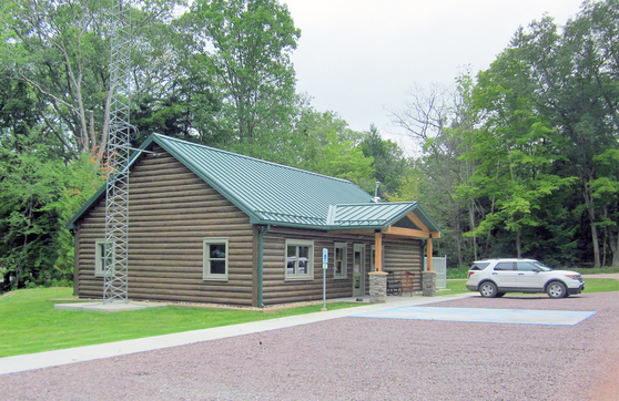 A wood building with metal roof and radio tower in a clearing of tall trees. A car sits in the small parking lot outside.