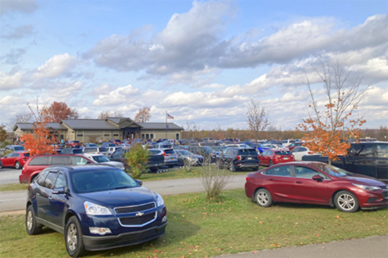 Many cars are parked in a parking lot in front of a building, with cars on the grass. Small trees and shrubs are planted among the cars.