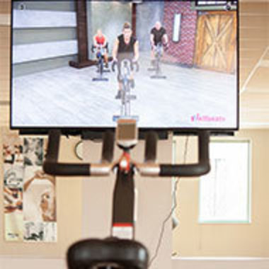 monitor showing stationary bike class is mounted on a stationary bike