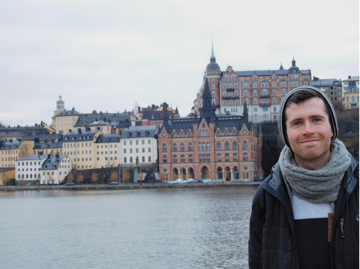 Daniel Riecker stands in front of river and picturesque buildings