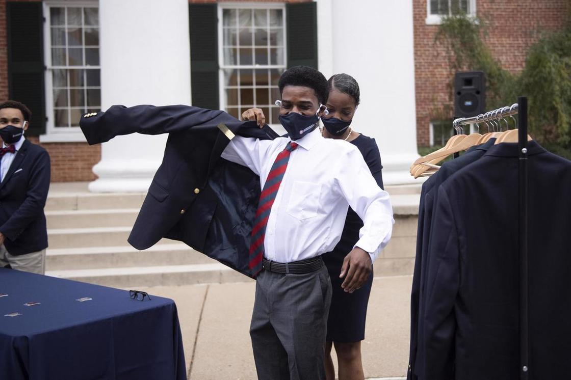 Young man receiving his Columns Society coat