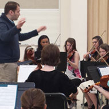 adult conducting ensemble of children on stringed instruments