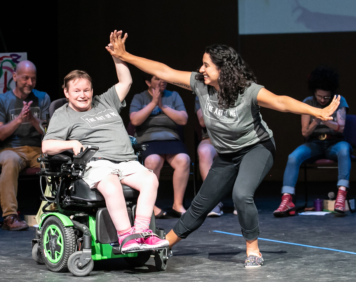 Image Description: Teaching Artists and adult participant-performers onstage during an Art of Me performance in August 2019. Center stage, a participant cooly raises their hand to give a high five to UA Teaching Artist Cristina Castro, a curly-haired Latina woman.