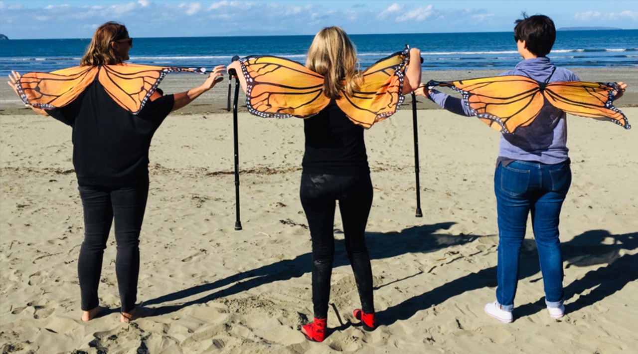 Image. Three friends and family stand at pacific ocean with butterfly wings, cleebrating survivorship.