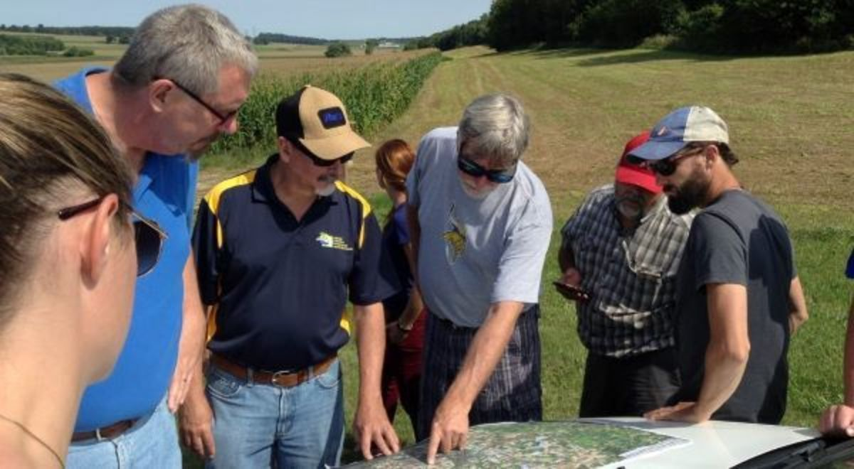 A group of people in the field looking at an ACPF output map