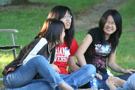 3 students sitting together laugh and chat