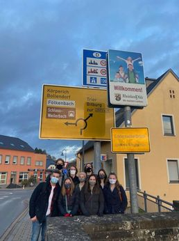 Students pose in front of a grouping of directional signs