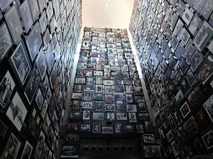 photo of three walls covered in photos, inside the US Holocaust Memorial Museum in Washington DC