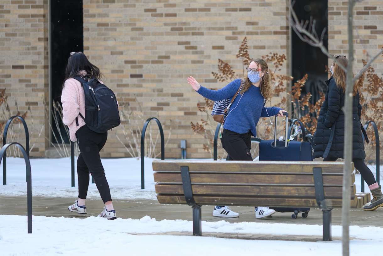 Students walking about on a sidewalk.