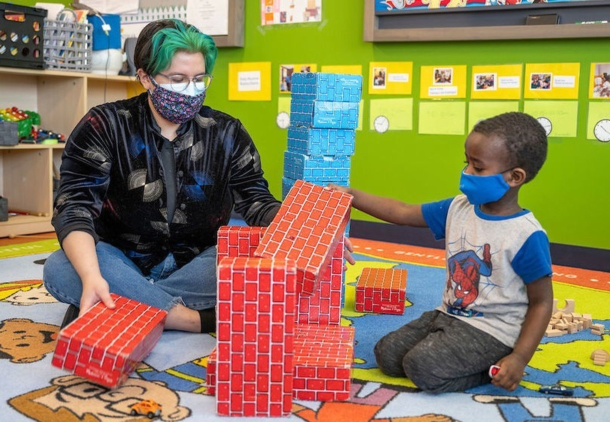 An adult is playing with a child and red blocks.