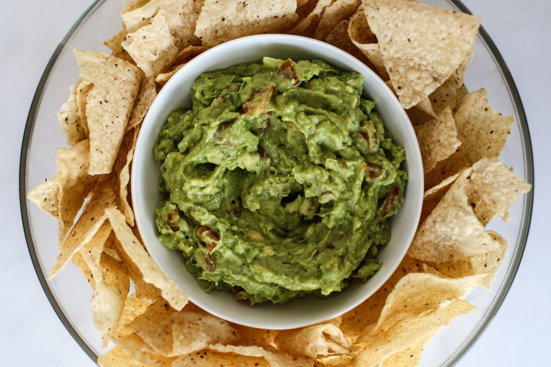Bowl of tortilla chips with guac in the middle