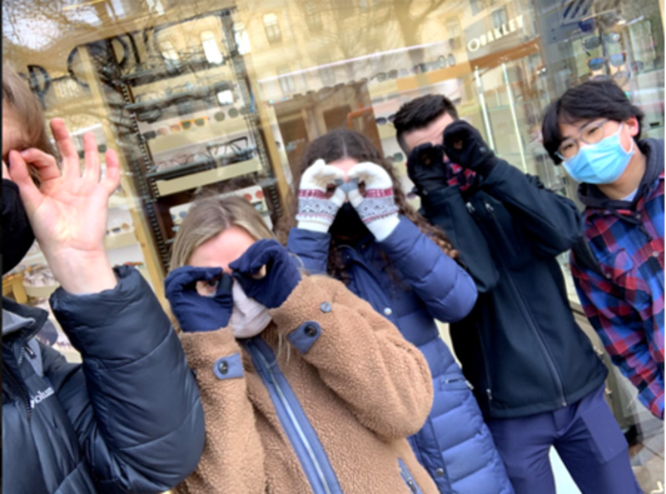 Team Belvaux poses with masks and gloved hands to make eyeglasses around their eyes