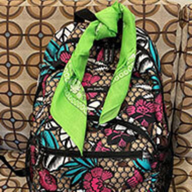 bookbag with a green bandana tied to it