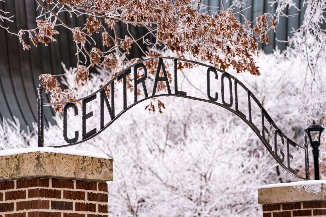 Photo of the Central College arch sign on the Peace Mall with ice and frost covered trees and Chapel in the background