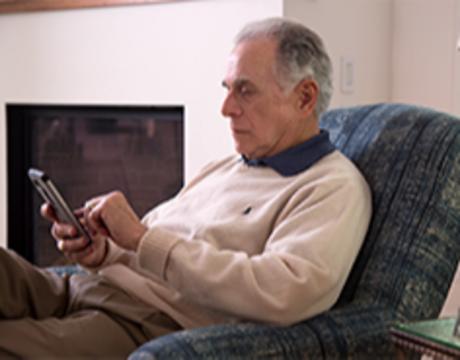 An elderly man sits in a chair.