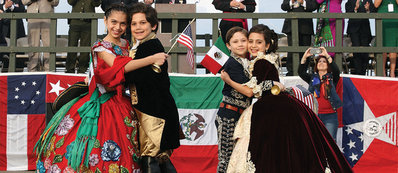 Children in traditional costumes from Mexico and 18th century America pose for a photo
