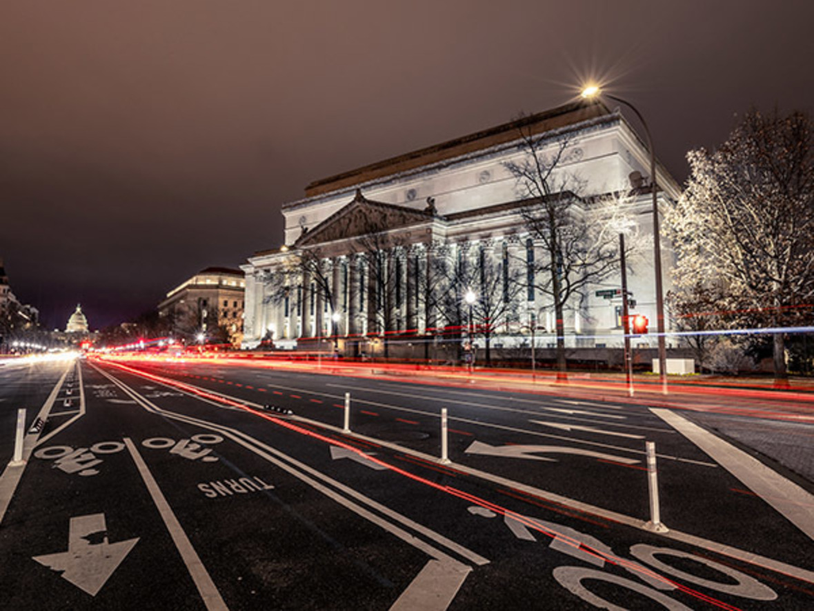 photo of US National Archives building at night with light trails from passing cars