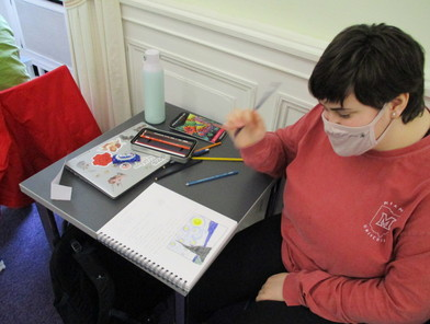 a masked student pauses and gazes at the open sketchbook on the desk