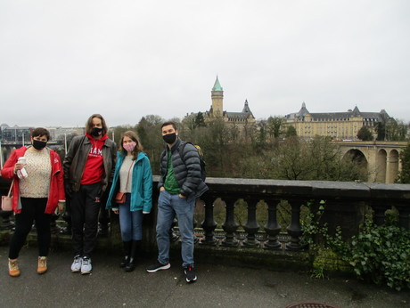 Masked MUDEC students pose on a bridge with Lux City in background