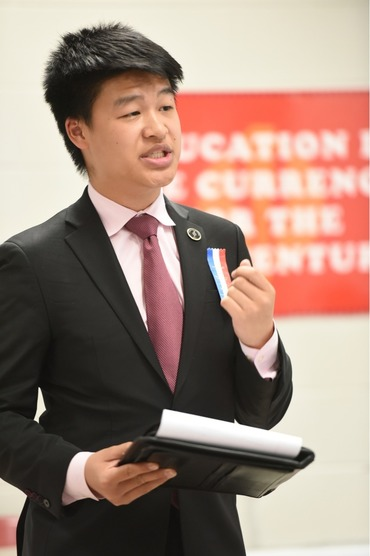 Student delivers speech, holding a padolio and gesturing with the other hand